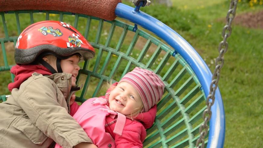 Spielende Kinder in einer Vogelnestschaukel